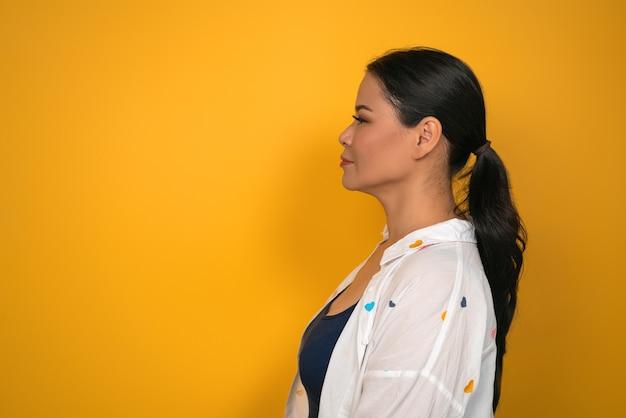 完璧な肌を持つ中年女性がコピースペースを見ています。黄色の背景に長い髪のきれいなアジアの女性の縦断ビュー。