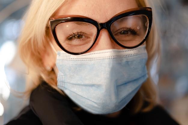 얼굴 보호 마스크와 안경 중간 나이 든된 여자가 초상화를 닫습니다