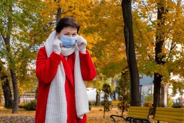 保護マスクを顔につけた中年女性が秋の公園を散歩