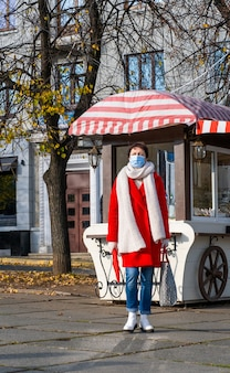 Covid-19期間中、顔に保護用マスクを付けた中年女性が街を歩く