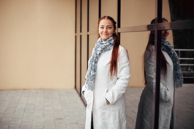 曇りの日に白衣を着た赤い髪の中年女性。