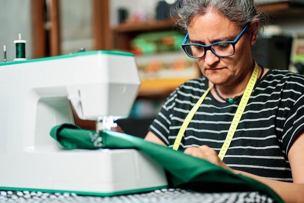 흰 머리를 가진 중년 여성이 집에서 재봉틀로 바느질합니다.