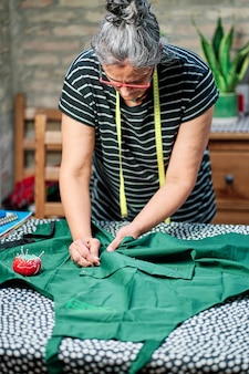 흰 머리를 가진 중년 여성, 안경을 쓰고 목에 테이프를 감고 집에서 바느질 테이블에서 일하고 있습니다.