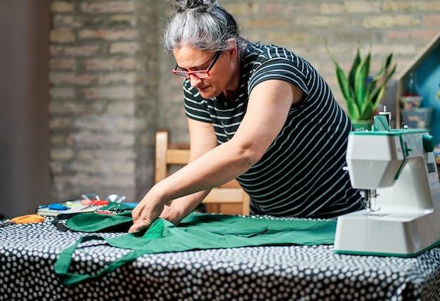 집에서 바느질을 위해 직물을 측정하는 안경을 쓰고 흰 머리를 가진 중년 여성.