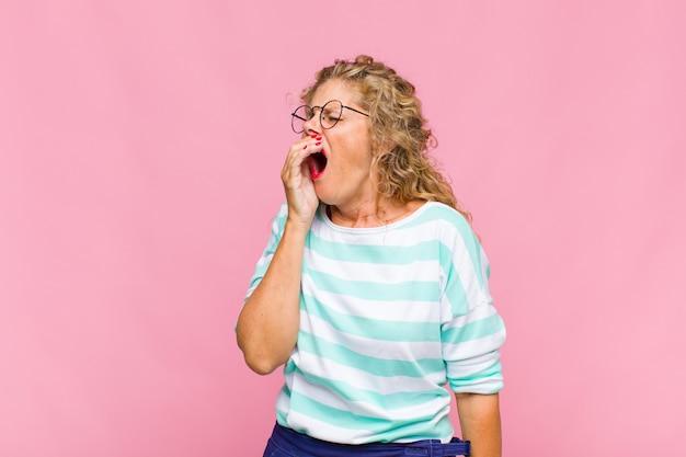 Женщина средних лет лениво зевает рано утром, просыпается и выглядит сонной, уставшей и скучающей