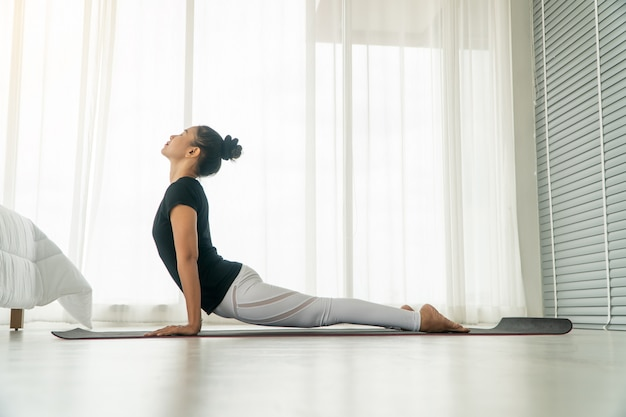 Middle aged women doing yoga in bedroom at the morning