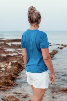 Женщины среднего возраста в синей футболке с пучком волос, стоящие на скале у моря на закате. съемка спины, макет футболки