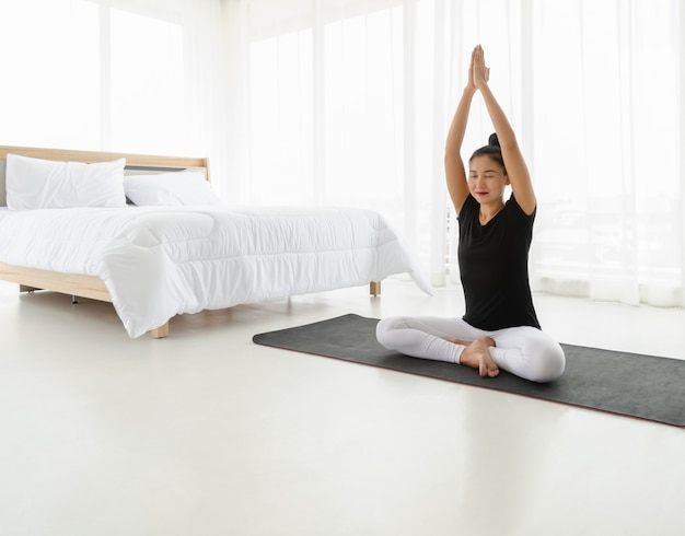 Middle aged women practicing yoga in easy seat pose (sukhasana) with raised hands above head pose.meditation with yoga in white bedroom