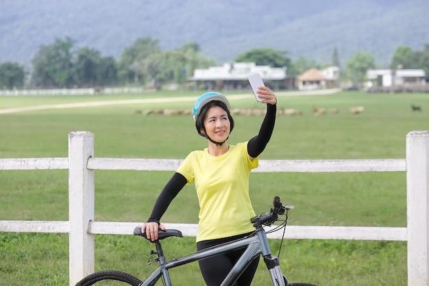 중년 여성은 자전거에서 휴대전화로 셀카를 찍는다