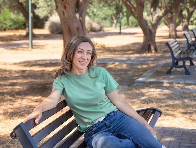 公園のベンチに座って、脇を見て、笑顔でtシャツとジーンズを着ている中年女性