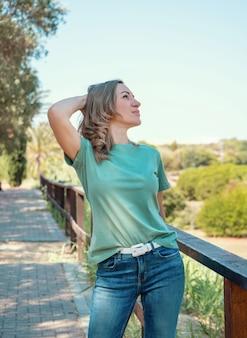 Tシャツとジーンズを着た中年女性は、頭を抱えて公園の屋外に滞在します