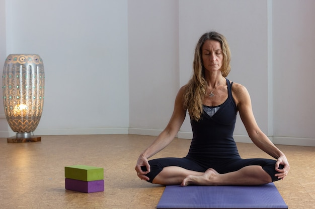 Middle aged yogi woman practices meditation sitting with eyes closed in lotus pose