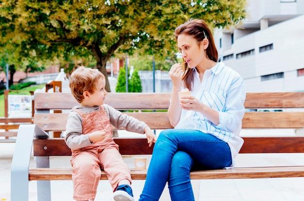 公園のベンチに座っている彼女の3歳の息子と一緒にアイスクリームを食べる中年の若い女性