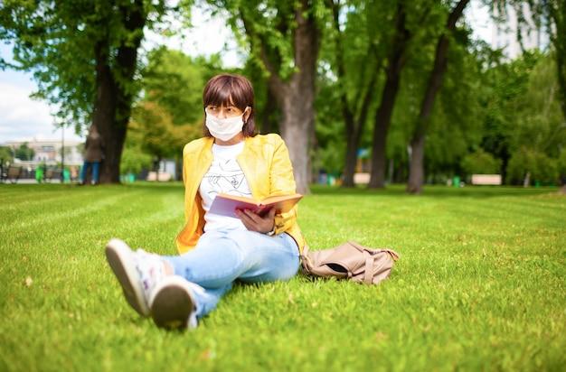 カジュアルウェアの中年の若い女性は白い医療マスクを着用します