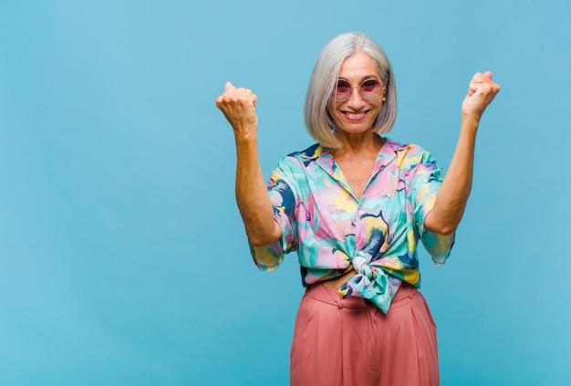 Крутая женщина средних лет празднует невероятный успех как победительница, выглядит взволнованной и счастливой, говоря: «бери!»