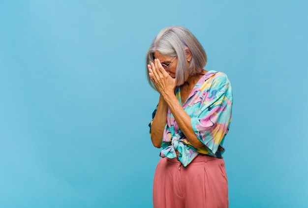 Крутая женщина средних лет закрывает глаза руками с грустным, разочарованным взглядом отчаяния, плачет, вид сбоку
