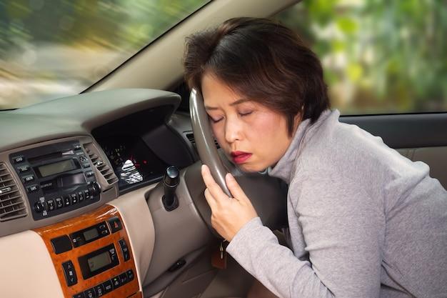 ステアリングホイールの後ろに眠い中年アジアの大人。輸送事故のリスク。