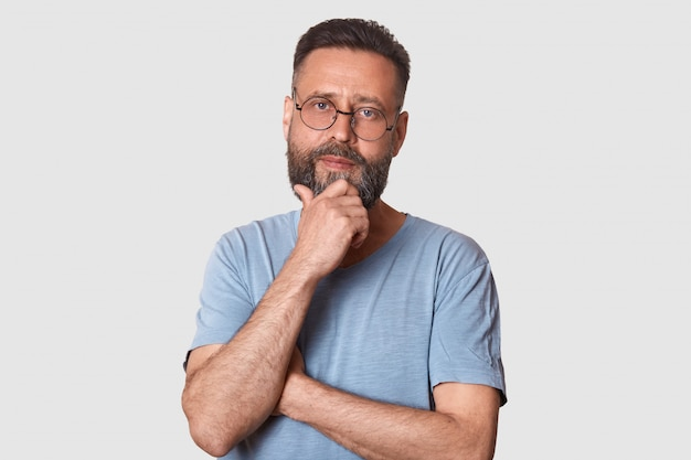 Middle bearded aged male with pensive facial expression, dressed gray cassual t shirt and round spectacles, keeps hand under chin, looks thoughtful, thinks abot new idea, has great plans.