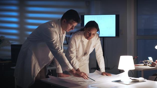 現代の研究室で制御電子スキームをチェックする2人の電子開発エンジニアの真ん中のクローズアップ
