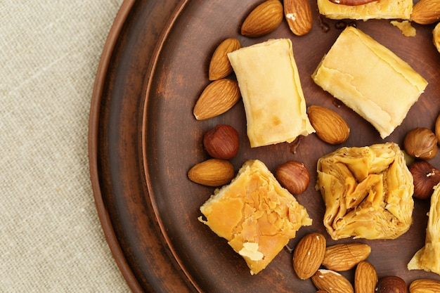 Middle east dessert with honey syrup and chopped nuts in a clay flat round plate