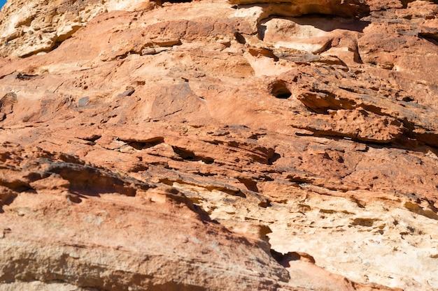 中東の山々の自然なオレンジブラウンのパターン、古代の砂漠の織り目加工の石