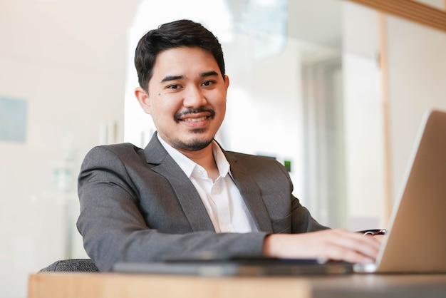 Ближневосточный взрослый бизнесмен сидит за столом во время работы на ноутбуке в офисе