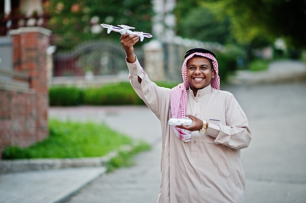Middle eastern arab business man posed on street with drone or quadcopter at hands.