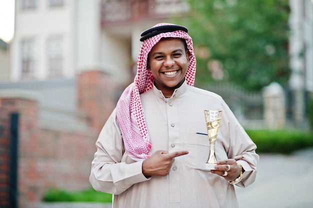 Middle eastern arab business man posed on street with golden cup at hands.