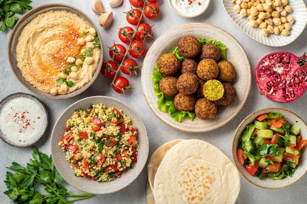Middle eastern or arabic cuisines, falafel, hummus, tabouleh, pita and vegetables on a concrete table, view from above