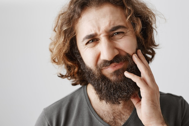 Middle-eastern bearded guy touching cheek and grimacing from pain, having toothache