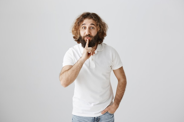 Middle-eastern bearded man shushing, asking keep secret or stay quiet