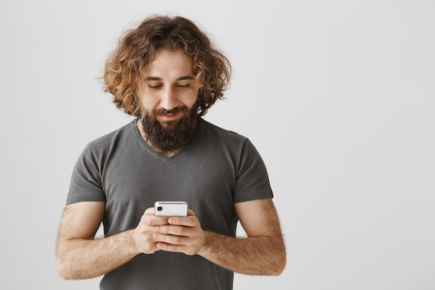Middle-eastern bearded man using mobile phone, texting and smiling happy