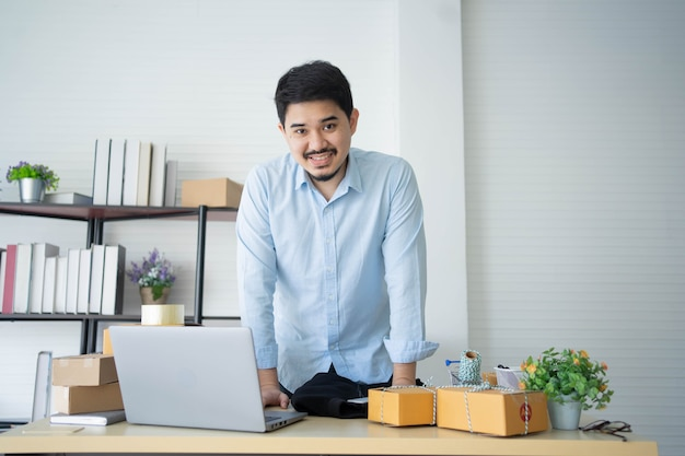 Middle eastern business owner stand in office with product packing boxes to delivery