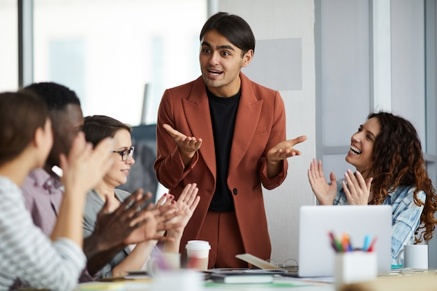 Middle-eastern businessman giving motivational speech in meeting