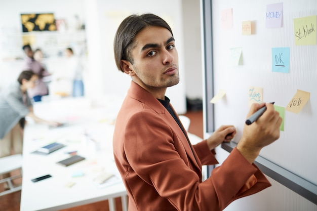 Middle-eastern businessman writing on whiteboard