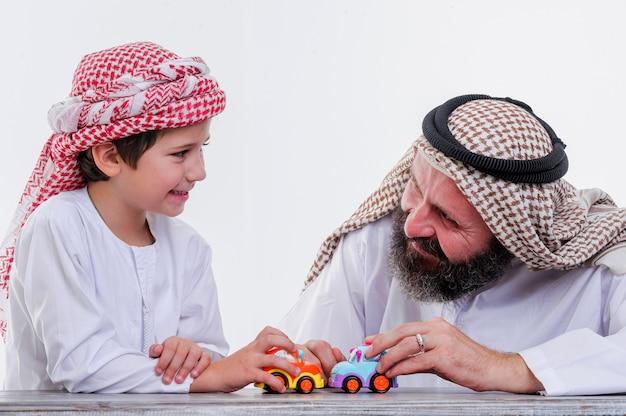 장난감 자동차를 가지고 노는 중동 아버지와 아들