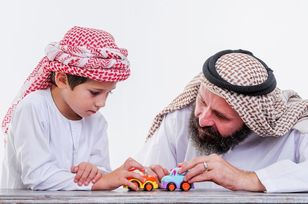 Middle eastern father and son playing with toy car
