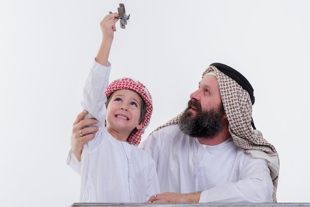 Middle eastern father and son playing with toy plane
