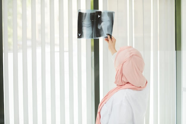 Middle-eastern female doctor looking at x ray