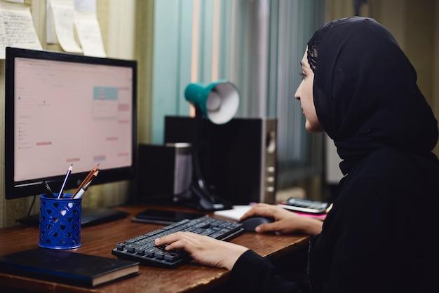 中東の女性起業家。忙しいアラビアの実業家。 pcで作業している伝統的なアラビアの服ヒジャーブまたはアバヤの女