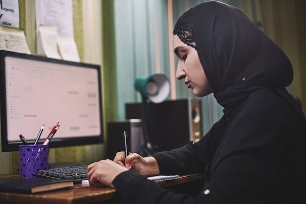 Middle eastern female entrepreneur. busy arabian businesswoman. woman in traditional arabian clothing hijab or abaya working on pc