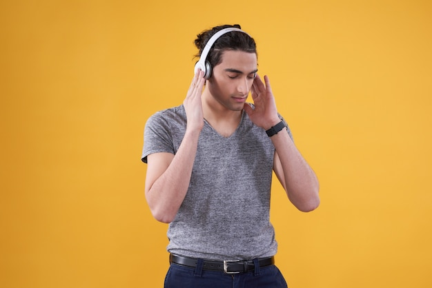 Middle eastern man listening to music isolated.