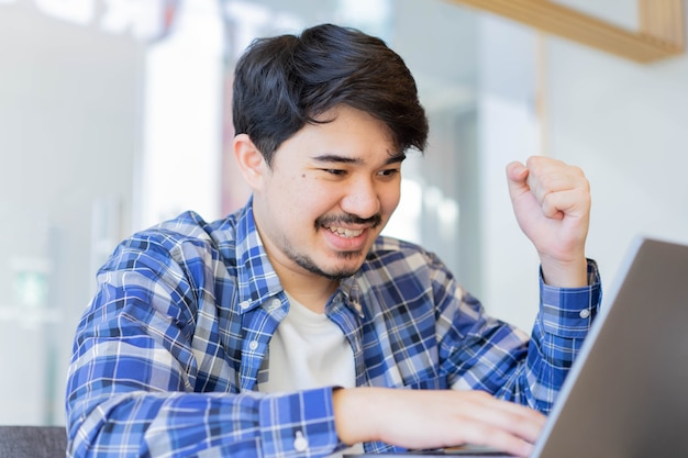Middle eastern man open laptop and sit in library while raise hand for celebration