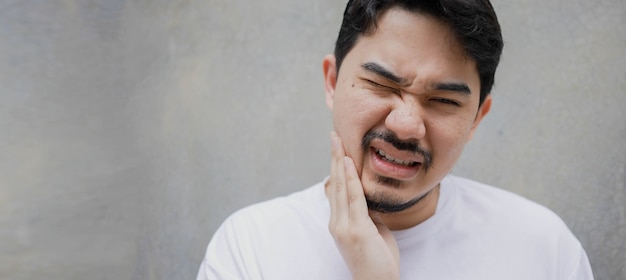 Мужчина с ближнего востока массирует щеку рукой от зуба мудрости