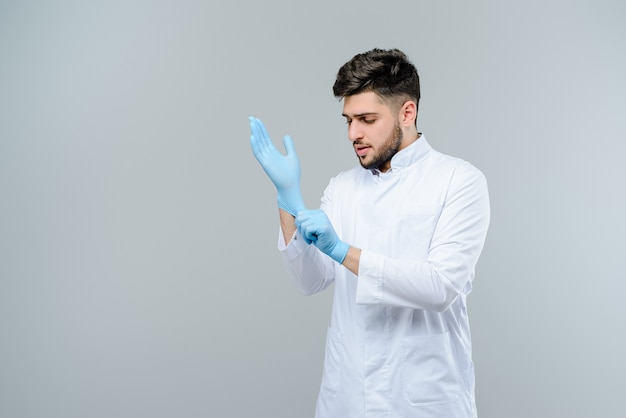 Middle eastern medical doctor in gloves isolated over grey background