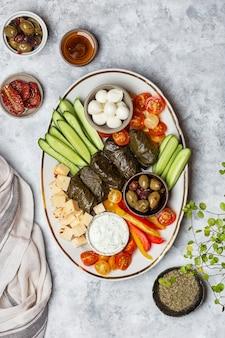 Блюдо ближневосточного мезе с овощами, сыром, толпой и соусом цацики