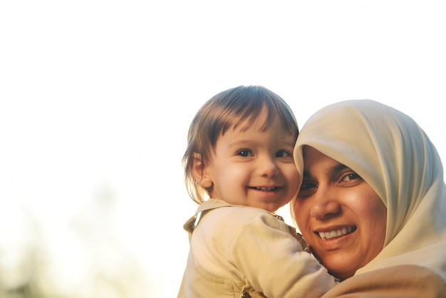 녹색 공원에서 그녀의 작은 아기와 함께 연주하고 팔에 그를 잡고 중동 이슬람 어머니