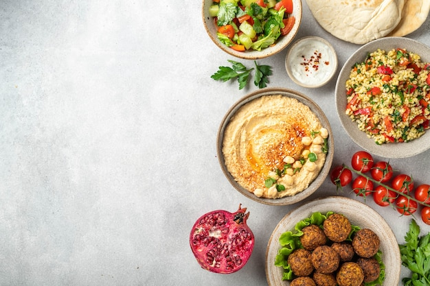 Ближневосточная или арабская кухня, фалафель, хумус, табуле, лаваш и овощи на бетонном фоне, вид сверху