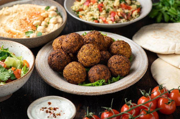 Ближневосточная или арабская кухня, фалафель, хумус, табуле, лаваш и овощи на деревянном фоне, выборочный фокус