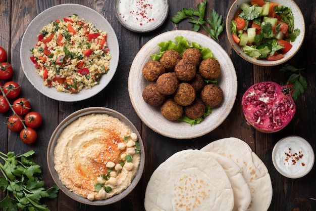 Ближневосточная или арабская кухня, фалафель, хумус, табуле, лаваш и овощи на деревянном фоне, вид сверху